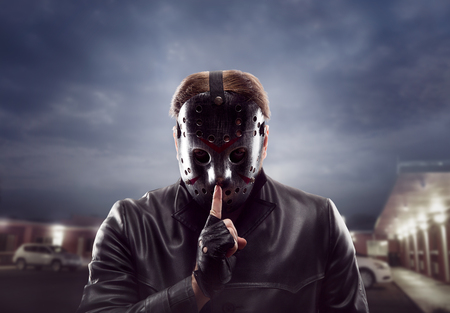Bloody maniac in hockey mask show do not talk sign Stock Photo
