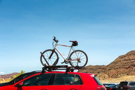 transporting: Car is transporting bicycle on the roof.