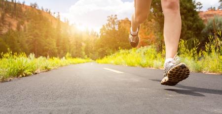 日没のクローズ アップでは、道路上のスポーツの靴の足。 写真素材