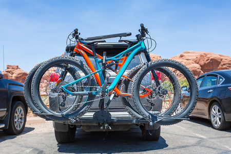 Bikes loaded on the back of a car.