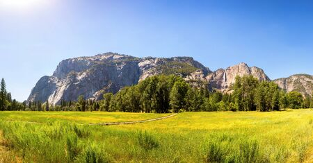 Meadow and trees surrounded by rocky mountains