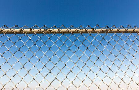 Rusty fence rabitz on the background of sky. Stock Photo