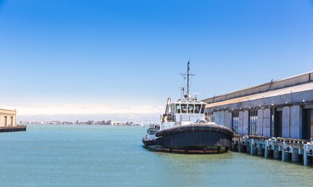 Tow ship in harbor of seaport. Stock Photo