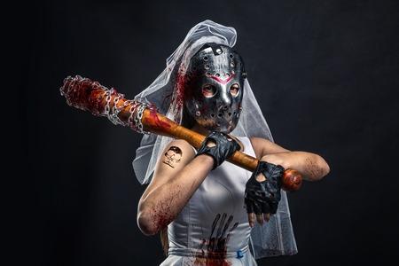 Serial murederer in wedding dress with bloody bat