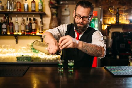 bartending: Barkeeper pouring alcoholic beverage in glass
