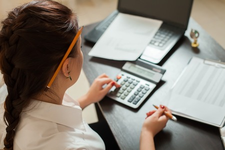 considers: Young female bookkeeper considers on calculator Stock Photo