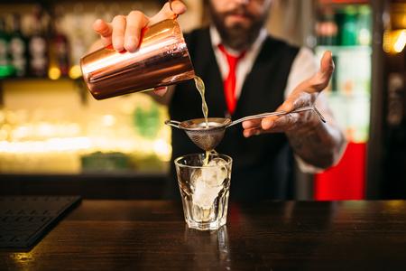 Barman flaring behind bar counter