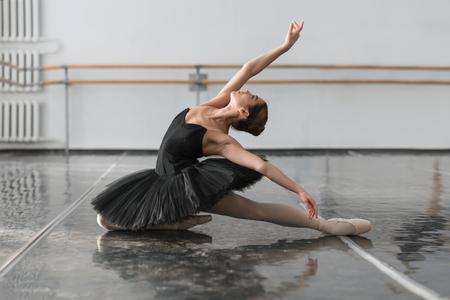barre: Beautiful ballerina sit on the twine in class