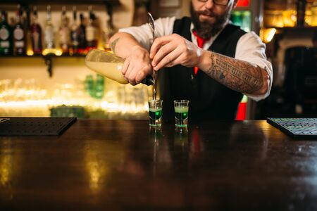 alcoholic beverage: Barkeeper pouring alcoholic beverage in glass
