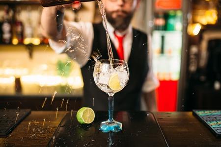 Barmixer gießt alkoholisches Getränk im Glas Standard-Bild - 73275595