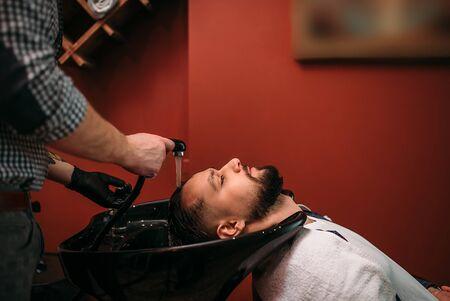 床屋は、クライアント人間の髪を洗う