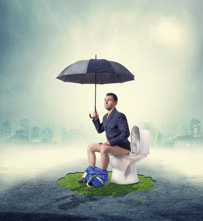 sitter: Man in fog sitting on toilet bowl with umbrella Stock Photo