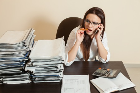 ady: Female accountant using cell phone at workplace