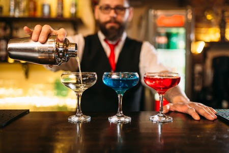 Bartender making alcohol beverages in nightclub Stock Photo