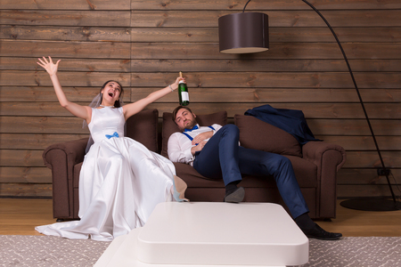 Drunk bride with bottle, groom sleeping on couch