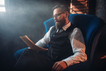 persona leyendo: Bearded writer in glasses reads handwritten text