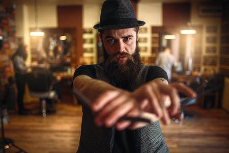 barber scissors: Barber in hat holding scissors and straight razor Stock Photo