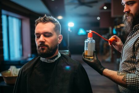 aftershave: Barber splashing client face by aftershave lotion Stock Photo