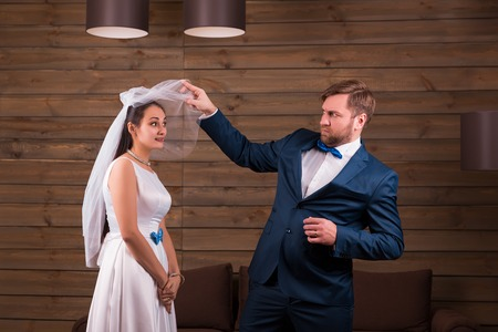 dress suit: Bride in dress and veil against groom in suit Stock Photo