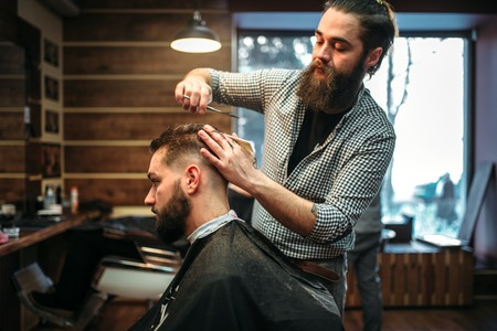 coiffeur: Bearded coiffeur cutting hairstyle by scissors
