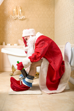 Drunk Father Christmas sitting on the toilet