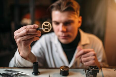 pinzas: Watchmaker holding with tweezers a gear of hours