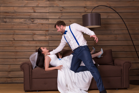 Groom trying to choke bride in white dress Stock Photo