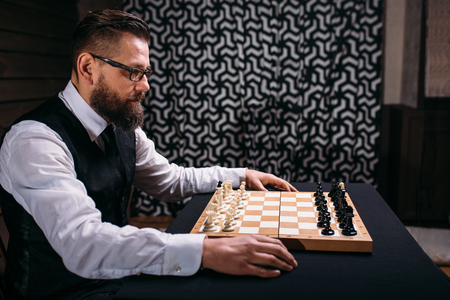 pawn adult: Male player against chess board with pieces set