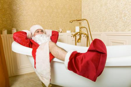 Funny drunk Santa Claus lies in a bath