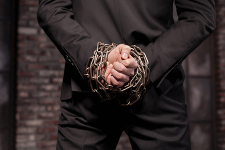 felonious: Silent murderer hands in iron chain, back view Stock Photo