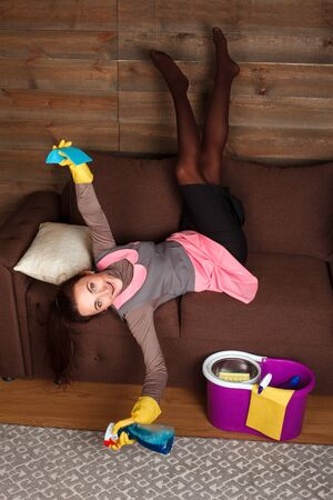 cleaning service: Woman in cleaning uniform poses on a couch Stock Photo