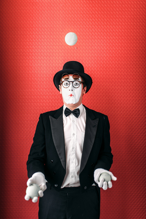Pantomime male actor juggles with balls