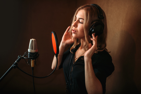 vocalist: Female singer recording a song in music studio
