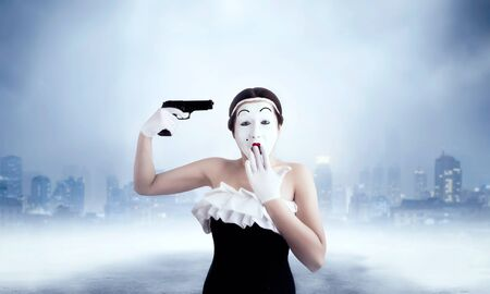 Mime female artist performing with gun