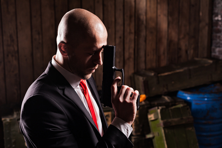felonious: Contract assassin in suit and red tie holds gun