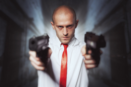 Bald hired killer in red tie aims a pistols