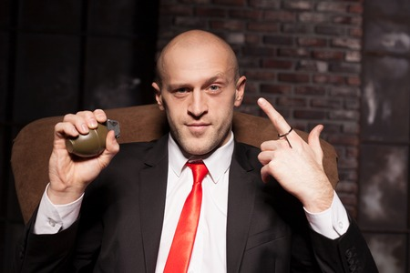 Killer in suit and tie ready to pull a grenade pin Stock Photo