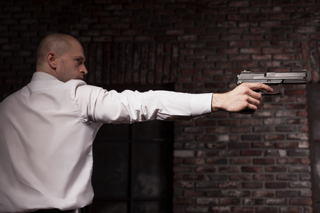 Serious hired murderer in red tie aims a gun Stock Photo