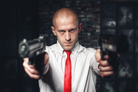 felonious: Bald hired killer in red tie aims a pistols