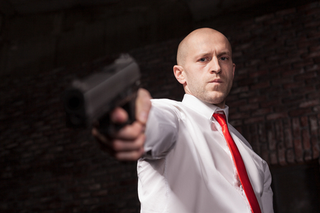 felonious: Serious hired murderer in red tie aims a gun Stock Photo