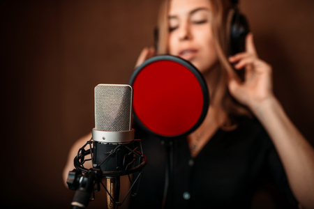 Female singer in headphones against microphone Stock Photo