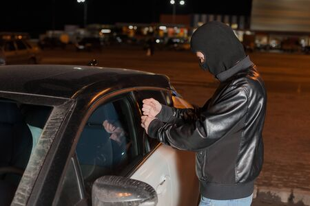 break the rules: Male carjacker trying to open car door with ruler