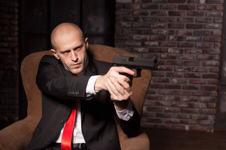 felonious: Bald killer in suit and red tie aims a pistol