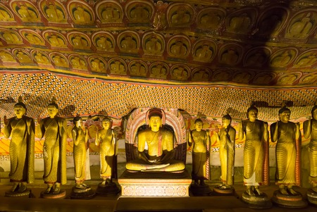 Ancient golden statues in buddha temple on Ceylon Фото со стока