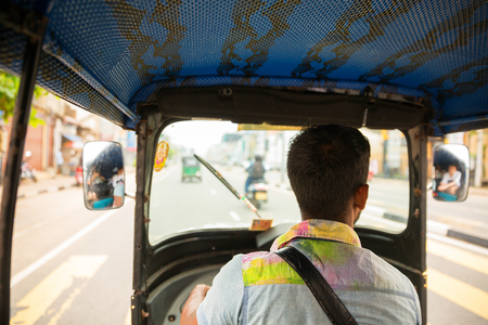 Tuk-tuk driver on road of Sri Lanka, view from car Stock Photo