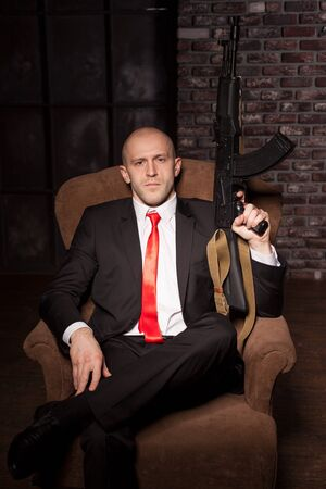 felonious: Contract killer holds automatic weapon Stock Photo