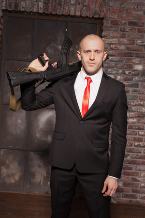 felonious: Assassin in suit and red tie holding machine gun Stock Photo