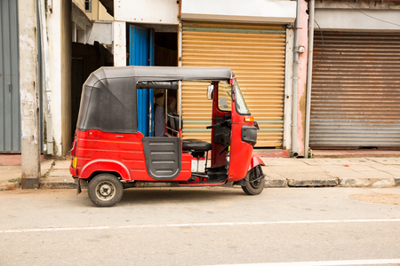 Tuk-tuk on road of Sri Lanka, side view