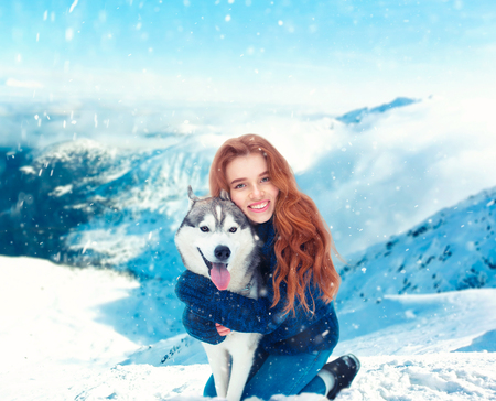 Smiling young woman hugs with husky Stock Photo