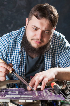 disassemble: Repairman fixing problem with soldering tool